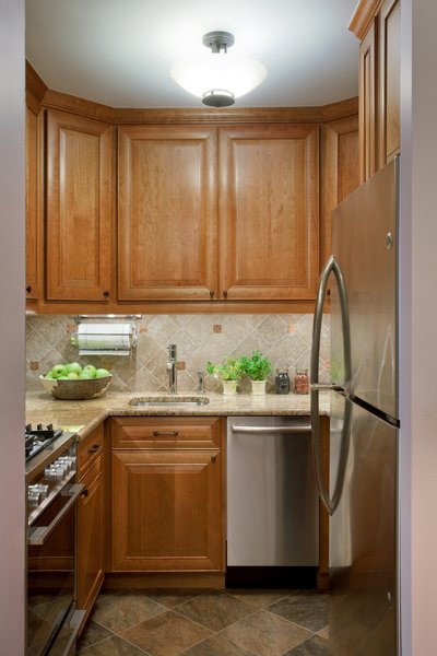 The kitchen, although small, packs a lot of storage punch! Going for a warmer more rustic look here, we used a tumble marble for the backsplash with inserts of a copper decorative tile that we placed throughout.  Photo  of Dog Lover's Apartment modern home