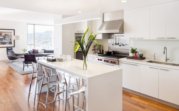A bright kitchen with a mirrored island & acrylic barstools add a glossy touch Photo  of Atwater modern home