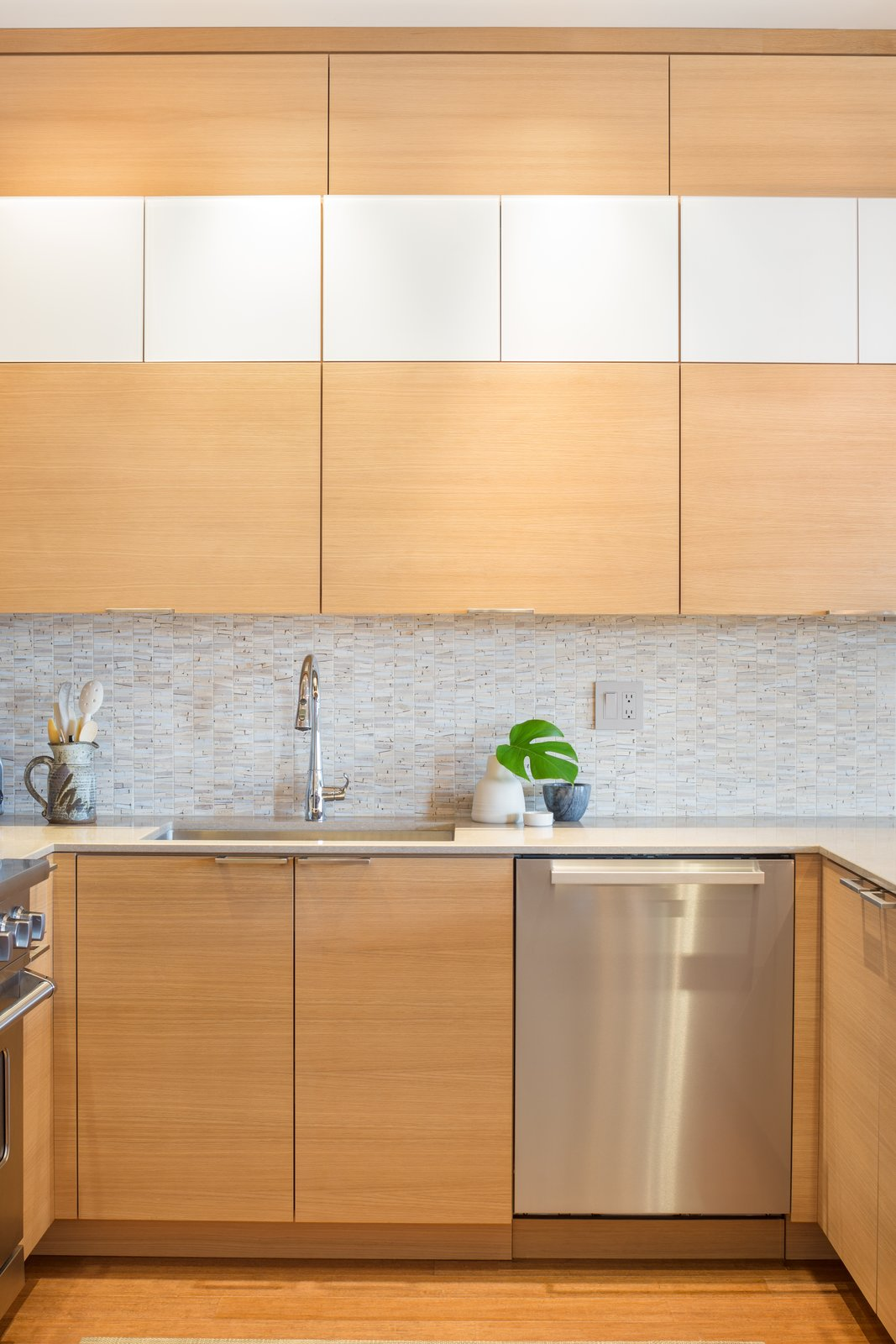 Pops of white enhance the warm wood tones  Tagged: Wood, Stone Tile, White, Medium Hardwood, Mosaic Tile, Recessed, Ceiling, Pendant, Refrigerator, Cooktops, Range, Undermount, and Kitchen.  Best Kitchen Cooktops Stone Tile Photos from Tanner Place