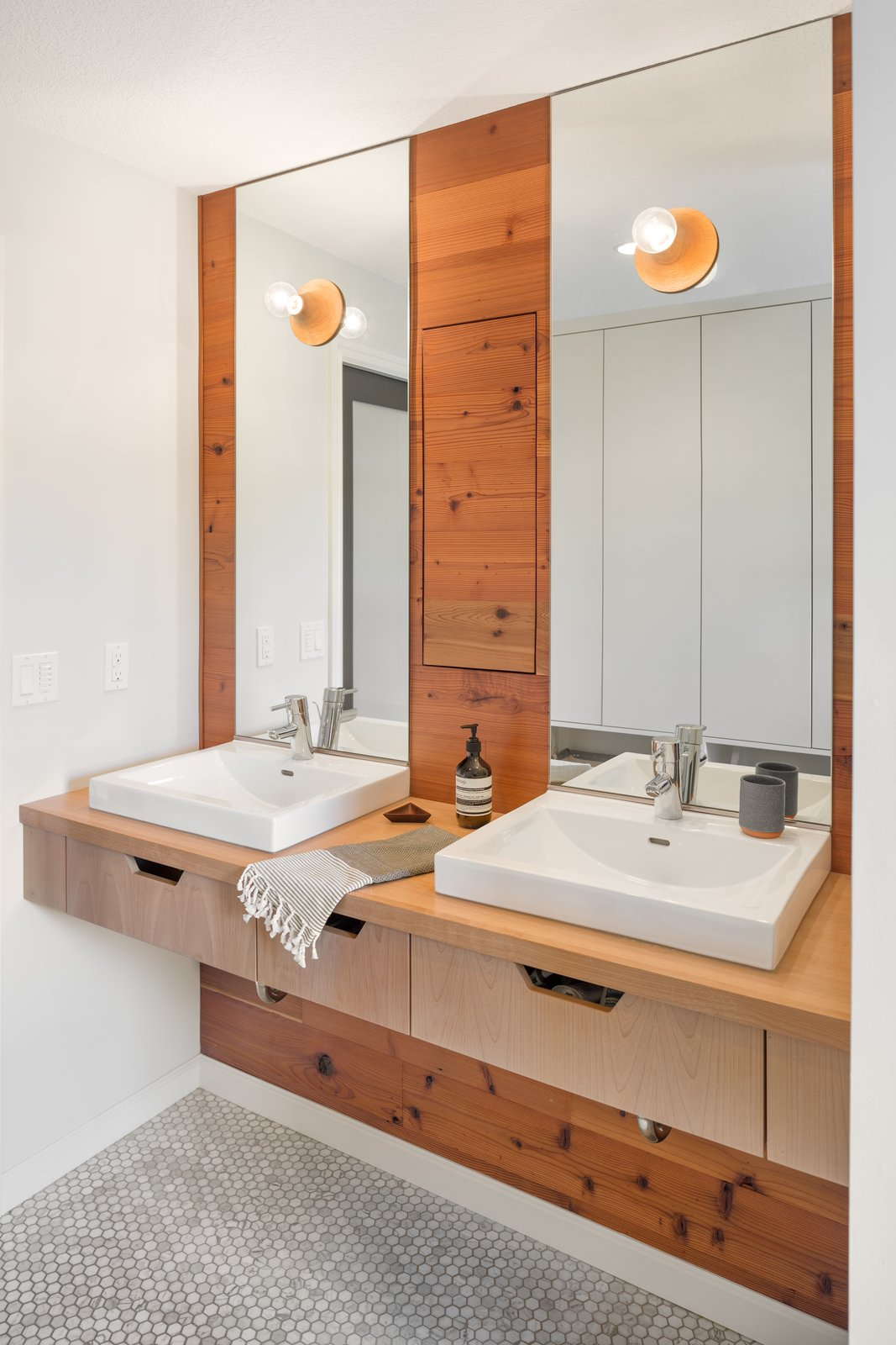 Mixed materials create a sleek, earthen inspired vanity  Tagged: Light Hardwood Floor and Bath Room.  Hurst Avenue by Guggenheim Architecture + Design Studio