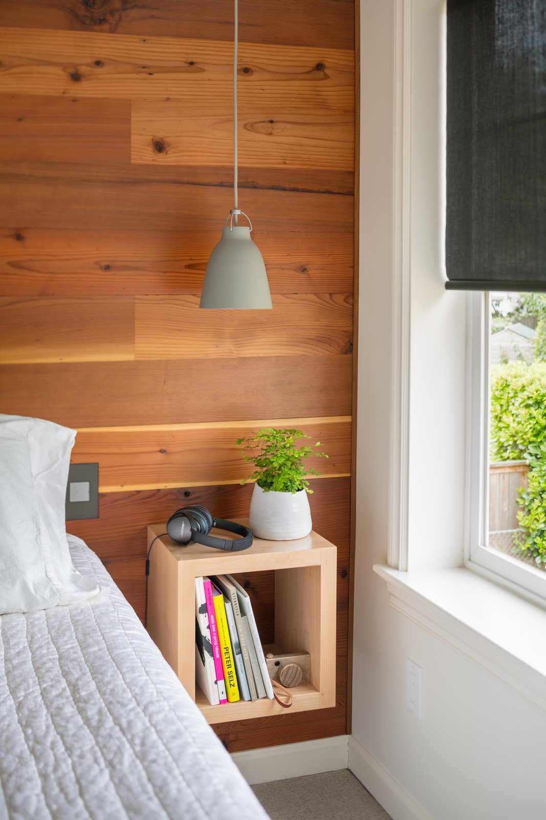 Floating nightstand keeps things organized and discreet Tagged: Wood Counter, Drop In Sink, Bedroom, Shelves, Bed, Toddler Age, Neutral Gender, Boy Gender, Night Stands, Ceiling Lighting, and Bedroom.  Hurst Avenue by Guggenheim Architecture + Design Studio