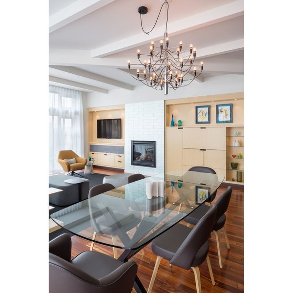 Modern home with storage, bar, medium hardwood floor, carpet floor, recessed lighting, standard layout fireplace, dining room, and pendant lighting. The custom dining table makes the space feel transparent yet formal Photo 5 of Block 90 Penthouse