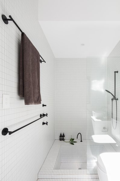 The bright, monochromatic bathroom with sunken tub provides a sense of tranquility and calm for the family. Photo 8 of Enmore House modern home