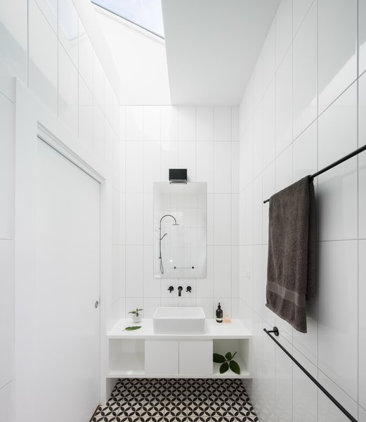 The ensuite bathroom shares a angular skylight with the main bedroom - allowing views to the sky and providing bountiful natural light. Photo 9 of Enmore House modern home