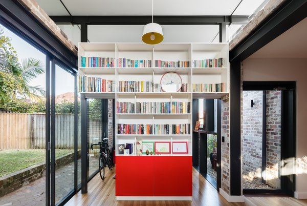 The home office/ guest room is defined by a free standing library and storage element with sliding door panels. A modest courtyard element provides additional natural light and ventilation. Photo 11 of Enmore House modern home