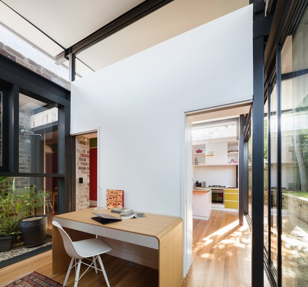 Solid sliding panels allow the home office and study to be entirely private or open up and connect to the living spaces of the home. The space doubles as a private guest room when required. Photo 12 of Enmore House modern home