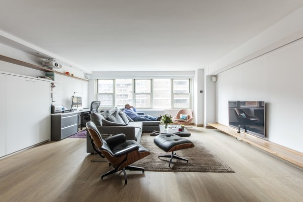 """Modern home with living room, chair, sofa, and medium hardwood floor. Not one to miss the tiniest of details, Frans had the entire apartment wired for temperature, lighting, and sound control he conveniently accesses via phone. They not only got the mudroom, but also managed to fold in multiple, flexible spaces to this origami apartment. Their new """"studio"""" might be the only one in all of Manhattan with as many separate rooms as they now have, perfectly positioned within one unique space. Photo 11 of Gramercy Studio Renovation"""