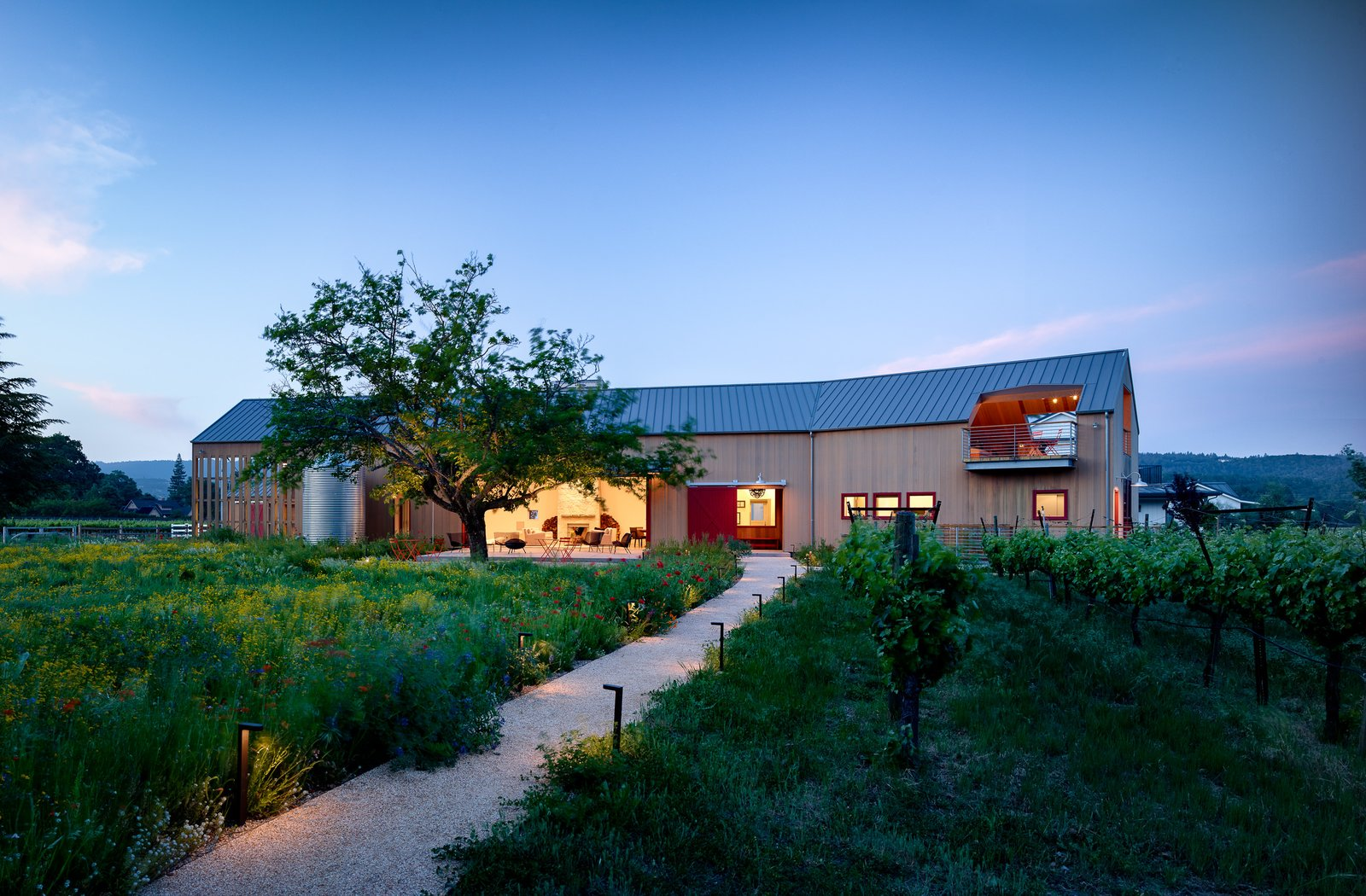 """Tasked with creating a multi-use guest pavilion on a relatively small Northern California vineyard lot that could also host sit down dinners for up to 60 people, designers at Anderson Architects started by asking the key questions:  """"Where should it be within the property?""""  """"How much floor area do we need for a 60 person dinner?"""" """"How much volume do we need for a basketball court?""""  """"We also always tell ourselves to look at the landscape first, let it dominate and lead it through. The building took the form of a large Napa Valley barn. Tagged: Outdoor, Trees, Front Yard, Walkways, Hardscapes, and Gardens.  Napa Barn by anderson architects"""