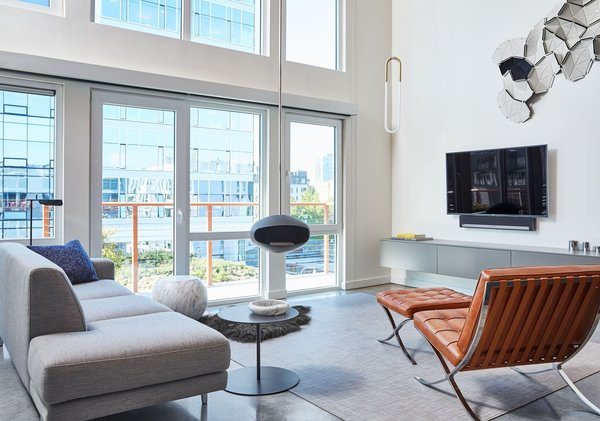 Modern home with living room, hanging fireplace, sofa, chair, and concrete floor. Photo 4 of South Lake Union Loft