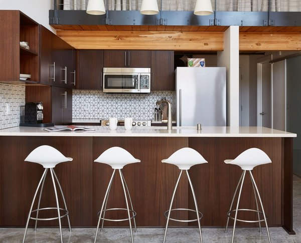 Modern home with kitchen, concrete floor, wood cabinet, and ceramic tile backsplashe. Existing kitchen with new furniture and accessories Photo  of South Lake Union Loft