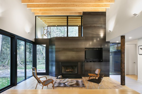 Modern home with living room, chair, standard layout fireplace, and light hardwood floor. Photo 8 of Courtyard House on a River