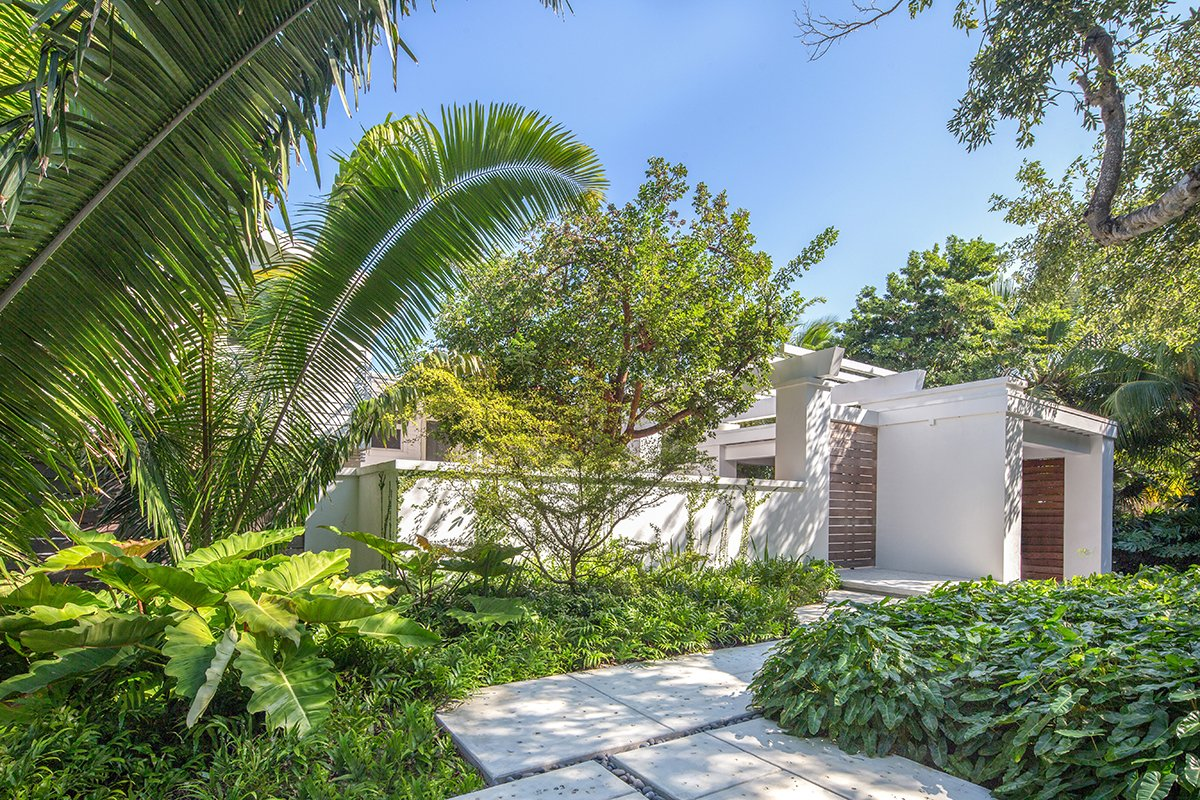 Tall tropical planting creates privacy and shade while the lush tropical foliage softens the look of the concrete building and pavers. The lignum vitae in front of the wall creates additional privacy for the owners. Tagged: Outdoor, Front Yard, Trees, Garden, Shrubs, Gardens, Hardscapes, Concrete Patio, Porch, Deck, and Walkways.  Photo 1 of 10 in The Best-Shaped House For Every Climate in the U.S. and Tips For Optimizing Sustainability from Waterfront Sanctuary