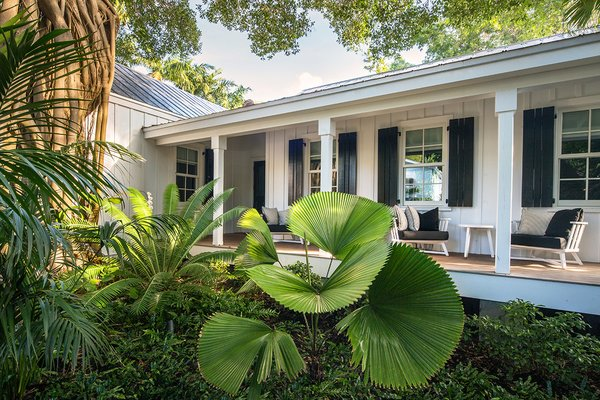 Modern home with outdoor, garden, hardscapes, gardens, trees, shrubs, walkways, front yard, decking patio, porch, deck, wood patio, porch, deck, and landscape lighting. Photo 2 of Key West Classic