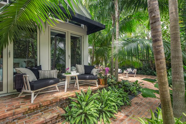 Modern home with outdoor, back yard, hardscapes, garden, trees, gardens, walkways, pavers patio, porch, deck, large patio, porch, deck, and landscape lighting. The main bedroom opens up to the garden and allows easy access to & from the pool. Photo 7 of Key West Classic