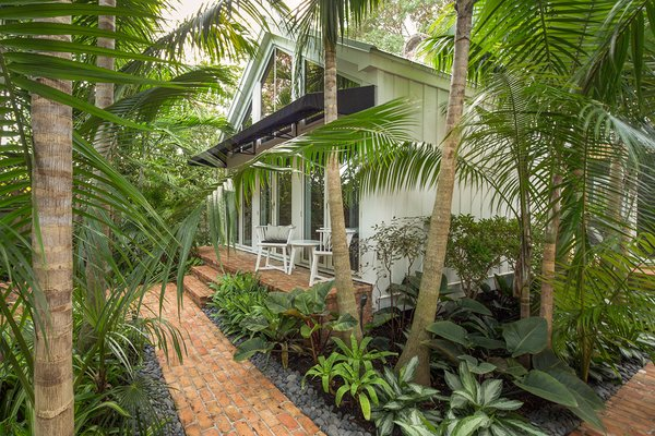 Modern home with outdoor, back yard, garden, trees, shrubs, hardscapes, gardens, large patio, porch, deck, landscape lighting, pavers patio, porch, deck, and walkways. Groupings of plantings help to keep the garden looking open and modern while still having a tropical feel. Photo 15 of Key West Classic