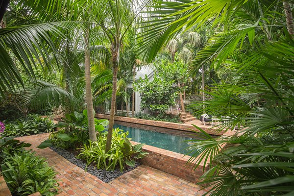 Modern home with outdoor, garden, shrubs, hardscapes, back yard, trees, gardens, walkways, swimming pool, standard construction pool, pavers patio, porch, deck, large patio, porch, deck, large pool, and landscape lighting. Photo 5 of Key West Classic