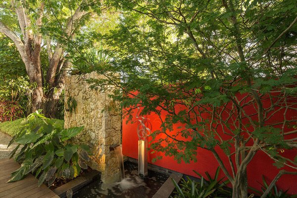 A fountain should always look good, even when dry. The bold red wall next to the natural stone veneer wall creates an interesting juxtaposition while a sculptural airy tree adds further interest while still maintaining the ability to see through it. Photo 10 of Von Phister modern home