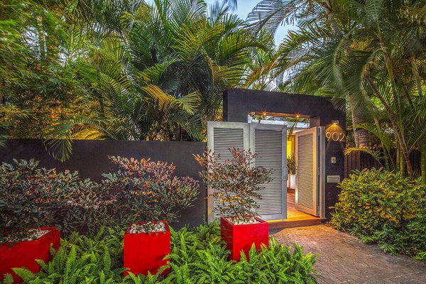 A dynamic entrance to the garden framed by mass plantings and bright sculptural containers sets the scene for the tropical garden behind the doors. Photo 13 of Von Phister modern home