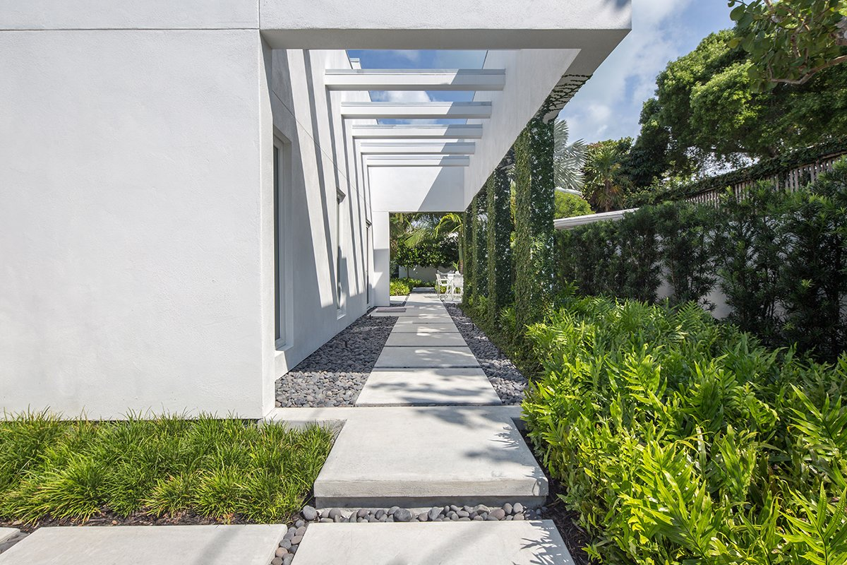 Poured in place concrete was used to mimic the structure of the home and the slight step up to to further emphasize the fact that one was entering into a different space. Planting was kept to minimal species and in groupings. Tagged: Outdoor, Shrubs, Hardscapes, Side Yard, Garden, Walkways, Concrete Patio, Porch, Deck, and Landscape Lighting. Tropical Minimal by Craig Reynolds Landscape Architecture