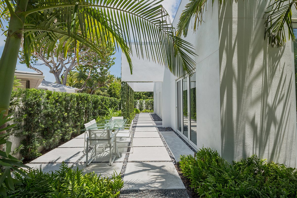 Indoor/outdoor living is a must in Key West. The main design philosophy of the overall design was to create areas outside that acted as their own special spaces and were an extension of the inside. Tagged: Outdoor, Shrubs, Trees, Side Yard, Walkways, Hardscapes, Landscape Lighting, and Concrete Patio, Porch, Deck.  Tropical Minimal by Craig Reynolds Landscape Architecture