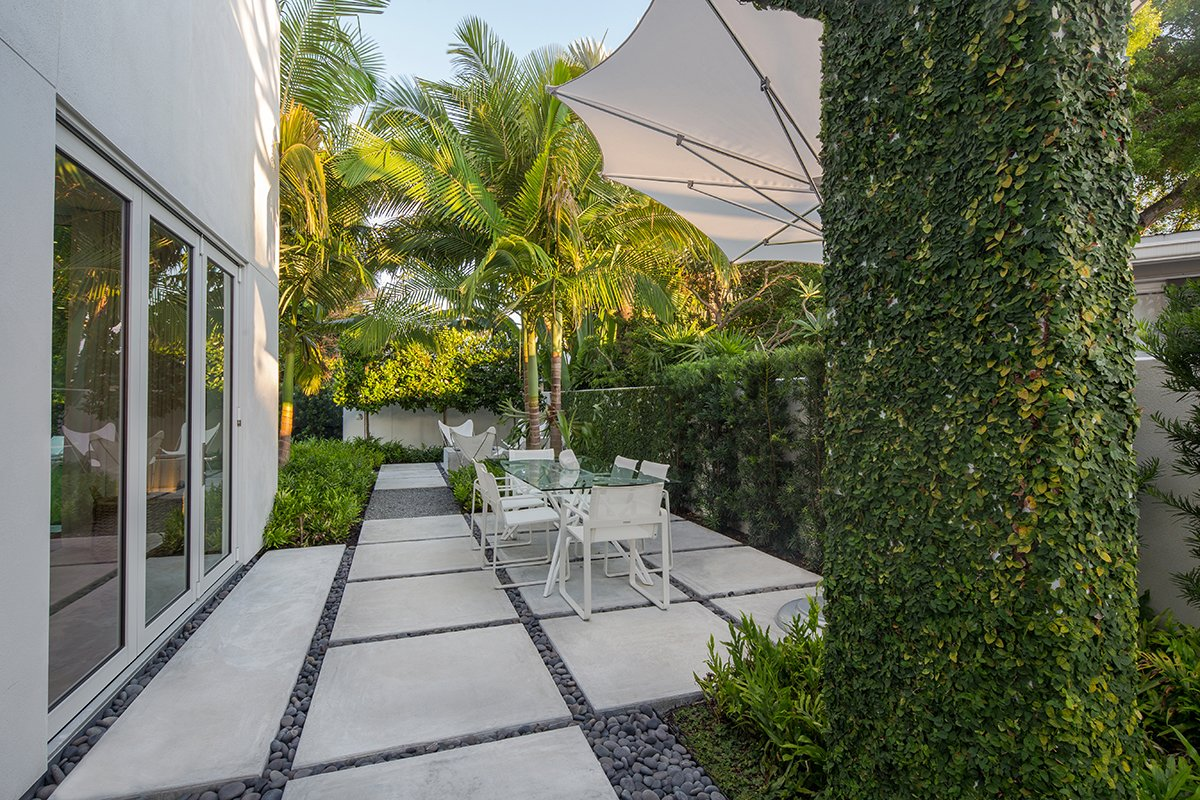 Indoor/outdoor living is a must in Key West. The main design philosophy of the overall design was to create areas outside that acted as their own special spaces and were an extension of the inside. Tagged: Outdoor, Side Yard, Garden, Trees, Gardens, Shrubs, Hardscapes, Walkways, Concrete Patio, Porch, Deck, Small Patio, Porch, Deck, and Landscape Lighting.  Tropical Minimal by Craig Reynolds Landscape Architecture