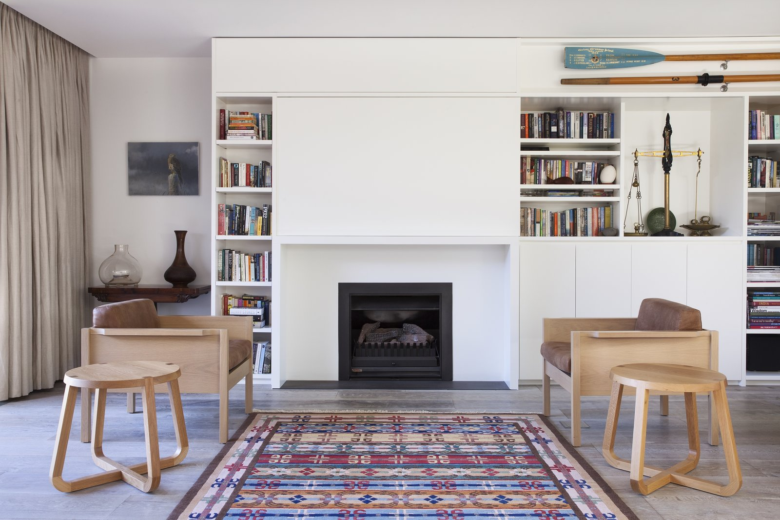 Tagged: Living Room, Standard Layout Fireplace, Chair, End Tables, Bookcase, and Light Hardwood Floor.  Photo 5 of 6 in A Timber-Clad Home in Australia Is a Striking Place to Grow Old In