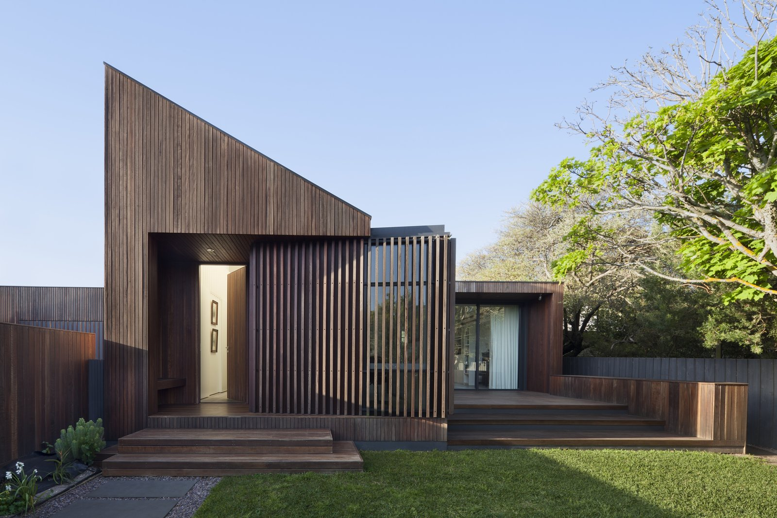 Tagged: Front Yard, Small Patio, Porch, Deck, Wood Patio, Porch, Deck, Doors, and Exterior.  Photo 1 of 6 in A Timber-Clad Home in Australia Is a Striking Place to Grow Old In
