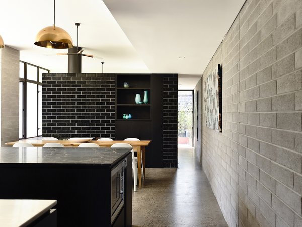 Modern home with dining room, chair, table, pendant lighting, concrete floor, and wood burning fireplace. Photo 7 of Elwood House