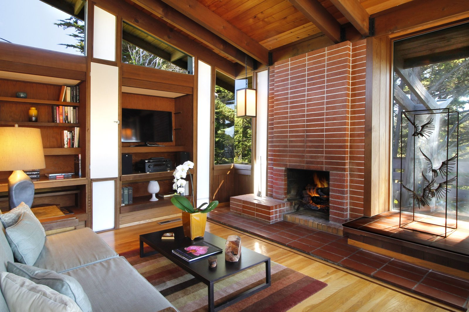 Tagged: Living Room, Standard Layout Fireplace, Wood Burning Fireplace, Table Lighting, Pendant Lighting, Medium Hardwood Floor, Rug Floor, Coffee Tables, Sofa, and Shelves.  Photo 10 of 11 in A Perfectly Preserved Midcentury Pad in Northern California Asks $1.975M