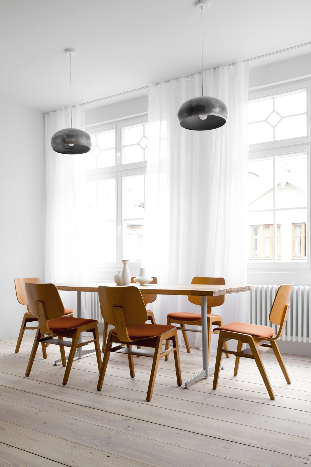 Tagged: Dining Room, Chair, Table, Pendant Lighting, and Light Hardwood Floor.  Best Photos from A Holiday Apartment in Poland With the Perfect Mix of Vintage and Custom Furniture