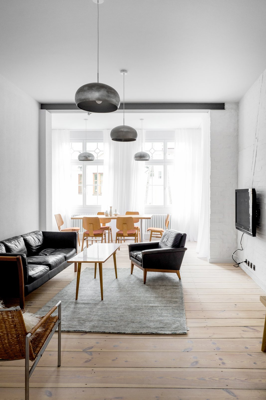 Tagged: Living Room, Sofa, Chair, Coffee Tables, Pendant Lighting, and Light Hardwood Floor.  Best Photos from A Holiday Apartment in Poland With the Perfect Mix of Vintage and Custom Furniture