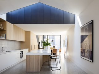 "Dwell's Top 10 Kitchens of 2017 - Photo 3 of 10 - Pandolfini Architects melds steel, concrete, and oak in an elegant, double-height rear addition to a 100-year-old residence. The goal of Dominic Pandolfini's renovation was clear. The architect, founder of Pandolfini Architects, and owner of this century-old home in the Port Melbourne neighborhood told est living: ""We wanted a house that was simple, timeless, and hardwearing. Despite the constraints of a long narrow site, we wanted to create some generous spaces that had a sense of drama."" Pandolfini did just that by leaving the front facade as is, then collaborating with contractor Duo Built to insert a two-story, rear addition that deftly combines steel, concrete, and oak."