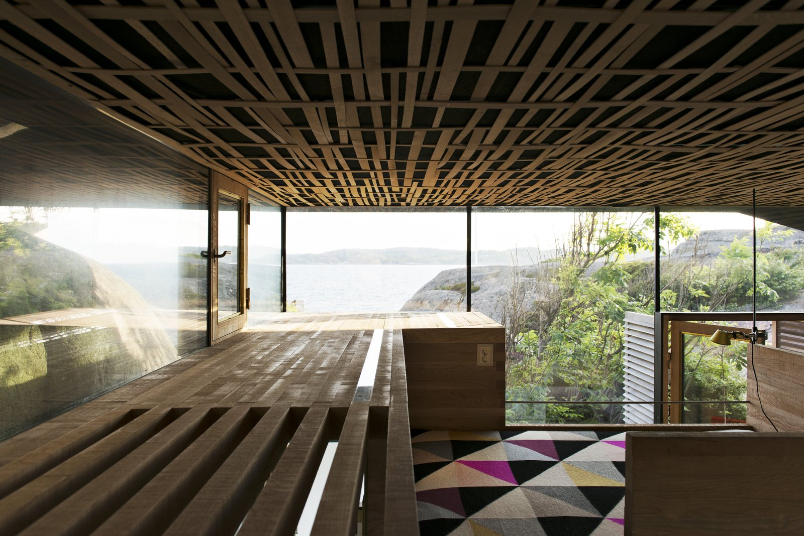 The interior walls are solid 50/50mm oak layered with a natural sawn texture, while the acoustic ceiling is covered with woven oak strips.
