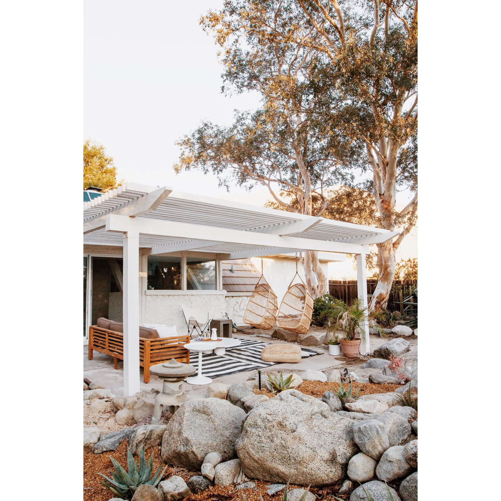 This pergola-covered seating area, complete with hanging chairs, is off the living room.