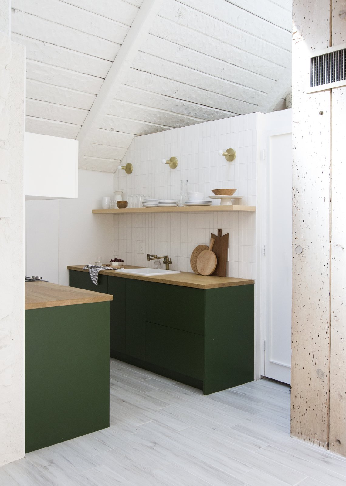 A view into the kitchen, which received IKEA cabinet boxes with Semihandmade drawer and door fronts painted Chard from Behr, by Samuel. The refrigerator is a KitchenAid model tucked under the butcher block counter and covered with a panel.