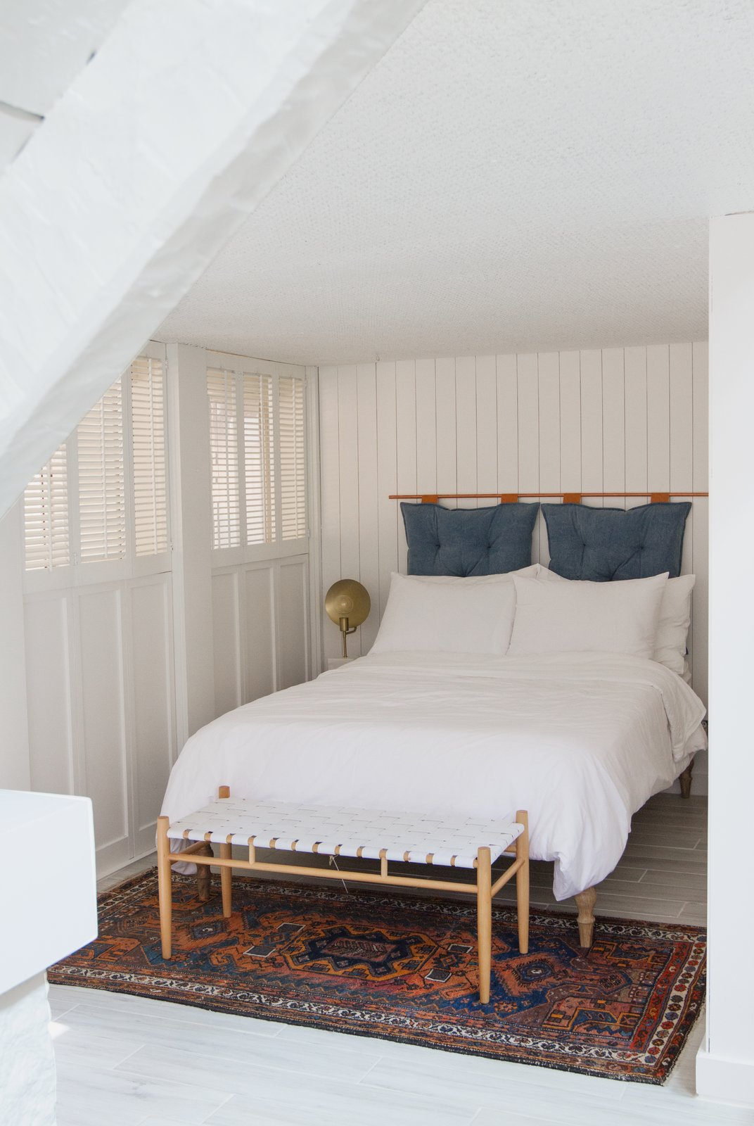 """Off the living room, Samuel uses this den as a second sleeping spot, or """"guestroom nook."""" Crumbling basket-weave texture was covered with painted wood paneling and the headboard is a DIY."""