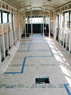 A Couple Convert An Old School Bus Into A Light and Efficient Family Home - Photo 3 of 12 - The team taped the layout on the floor and carefully installed the framework for the home.