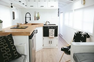 A Couple Convert An Old School Bus Into A Light and Efficient Family Home - Photo 8 of 12 - For the L-shaped kitchen, the family chose an under-counter fridge/freezer unit in order to have more counter space. The 23-inch Vigo sink is deep enough to bathe a baby, or hide dirty dishes.