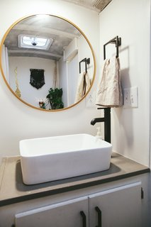 A Couple Convert An Old School Bus Into A Light and Efficient Family Home - Photo 10 of 12 - The Mayes did not want to separate the fixtures in the bathroom, so this one hosts the sink, toilet, and a shower. The brass mirror bounces light in the small space.