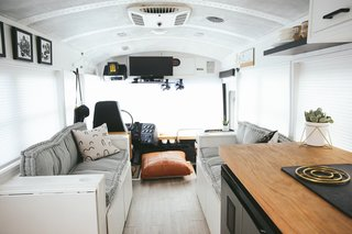 """A Couple Convert An Old School Bus Into A Light and Efficient Family Home - Photo 5 of 12 - Above is a look at the living area. The couches can seat the entire family, and can also be converted into a full bed, if needed. There is storage in the bases of the couch and a shoe shelf by the front door. """"This has been such a blessing and has helped us to keep the bus organized,"""" the Mayes Team explains."""