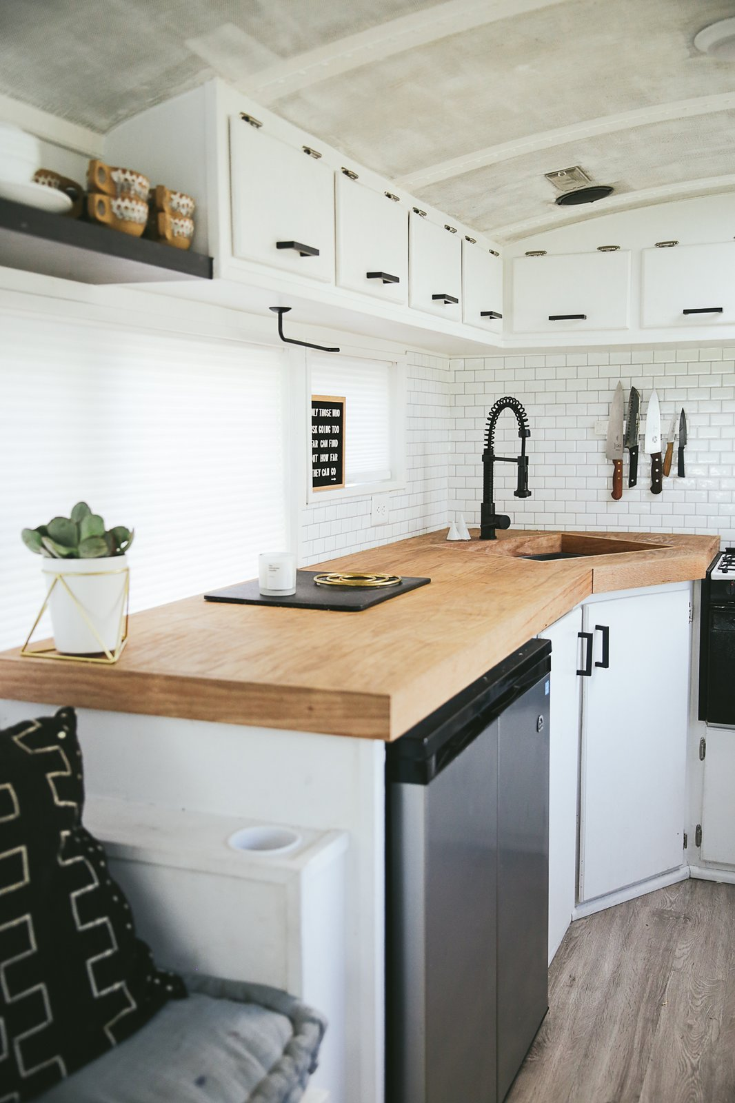 The countertops are birch-wrapped plywood. The matte black hardware and faucet punctuate white cabinets and peel-and-stick tile. The floating shelf holds dishes. There is one set for each member of the family so dirty dishes can't pile up. A magnetic knife strip and mounted paper towel holder saves counter space. The dish rack is folded and stored under the sink when not in use.