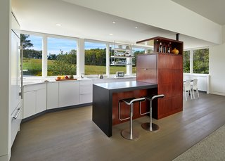 """A Modern Farmhouse Blends Community-Minded Living With the Country Landscape - Photo 3 of 8 - """"Although it looks like an inoperable window, these allow for ventilation,"""" Wiedemann said of the glazing lining the kitchen and dining areas. The architects opted for Marvin Casement Venting units in custom-widths."""