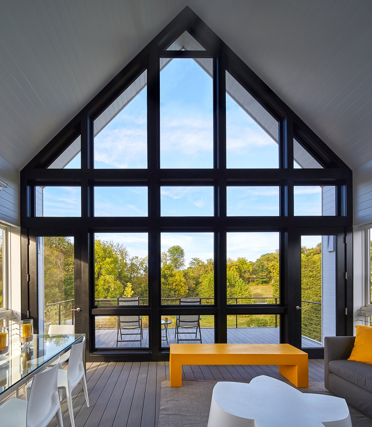 """This large screened porch is a favorite destination of the homeowner. """"She spends a lot of time on the screened porch because it straddles the meadow and the mountains,"""" said Wiedemann. """"And it's directly accessible from the living area and the kitchen."""" Tagged: Windows and Metal.  Best Windows Photos from A Modern Farmhouse Blends Community-Minded Living With the Country Landscape"""