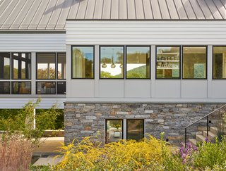 """A Modern Farmhouse Blends Community-Minded Living With the Country Landscape - Photo 6 of 8 - According to the architects, the screened porch panels (on the left) were site-built by the contractor to have similar dimensions as the Marvin windows (to the right). Dramatic black sashes unite the facade. Thin mull covers between window units blend with the exterior siding, """"which afforded a consistency that we were after,"""" said Wiedemann. Native stone on the foundation is similar to old Virginia farmhouses."""