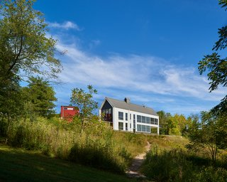 A Modern Farmhouse Blends Community-Minded Living With the Country Landscape - Photo 2 of 8 - A view of the back side of the two-story home reveals its dramatic glazing, which provides both levels with far-flung views into the site.