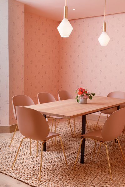 A meeting room swathed in pink, with matching un-upholstered Beetle chairs, designed by GamFratesi.