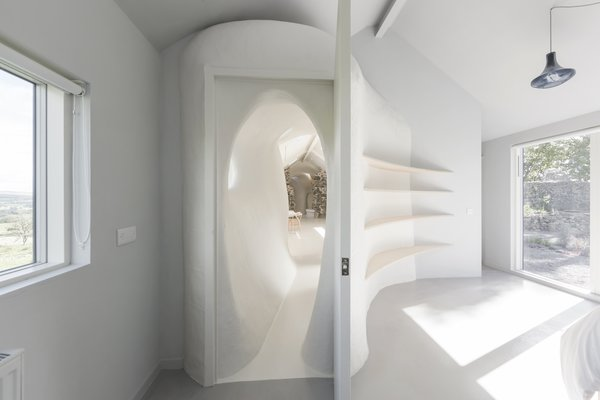 This shows how the freeform wall surfaces interplay with more crisp and square geometries of doors and windows.