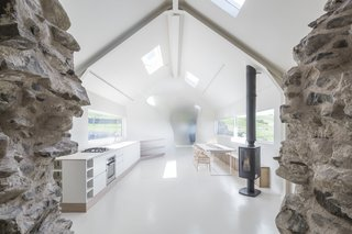 This Renovated Scottish Farmhouse With Sinuous Interior Walls Is a Jaw-Dropper - Photo 3 of 8 - The public area of the home includes a kitchen, study, sitting room, and dining area.