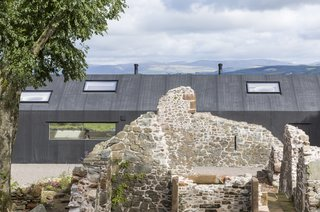 This Renovated Scottish Farmhouse With Sinuous Interior Walls Is a Jaw-Dropper - Photo 1 of 8 - The building's modern exterior cladding contrasts dramatically with the existing ruins.