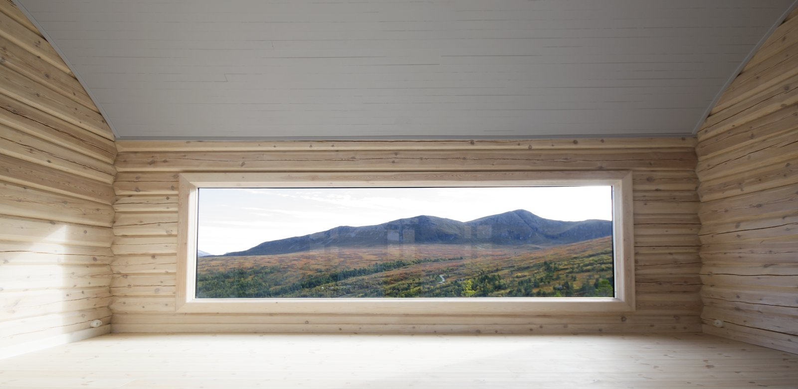"The panorama window in the barrel-vaulted living room. ""The low position of the window emphasizes that this is a room to sit and relax,"" says the architects. This room was built with 19th-Century notched logs."
